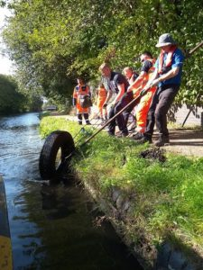Canal clean-up, volunteers pulling a tyre from the canal